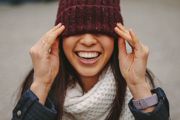 Portrait of a smiling woman with her face covered with a winter