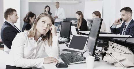 Portrait of unhappy girl in modern open plan office on backgroun