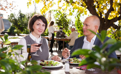 Couple in love drinking red wine at open-air restaurant