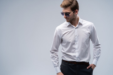 portrait of a young fashion man wearing sunglasses on grey background.
