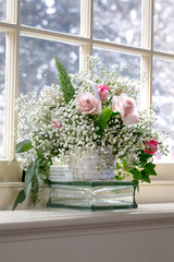 Pink roses in basket on window sill snowing
