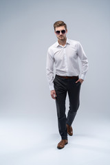 young man in sunglasses looks to side while walking on gray studio background.