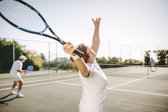 Senior woman making a serve while playing tennis