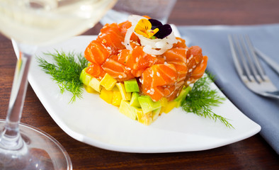 Cube of delicious salmon tartare garnish with avocado on plate at cafe