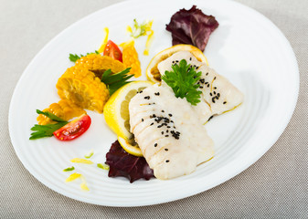 Codfish prepared on steam , served with boiled corn, herbs and lemon