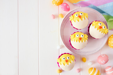 Hatching spring chick cupcakes. Flay lay side border with copy space against a white wood background.