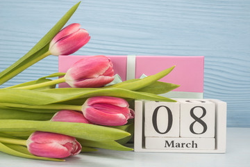 Bunch of spring tulip flowers, gift box and wooden cubic calendar