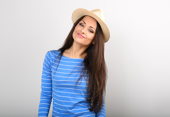 Friendly casual calm woman in blue top and straw hat looking happy with long volume hairstyle