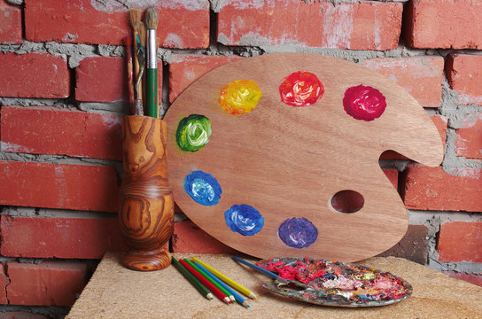 Art palette and brushes in a vase on a brick wall background