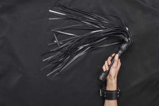 Explore each other's. Top view of female hands in black leather handcuffs holding a whip against of black silk.