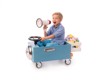 Child and Easter. A young blond boy rides a small blue toy car and carries a box of colorful eggs, holding a megaphone in his hand. Waist up portrait, facing camera. Studio photos.