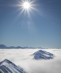 Mountain peaks covered in snow above clouds in La Plagne, French Savoy Alps. Winter scenic scenery, blue sky and stunning views.