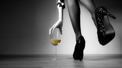 Beautiful girl legs and a glass of alcoholic beverage, black white photo, golden champagne in a glass
