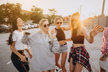 Four young women dance in a car park