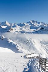 Unidentified skiers skiing on a ski slope in pristine alpine landscape. Calm and tranquil winter scenery in French Savoy Alps, ski resort La Plagne