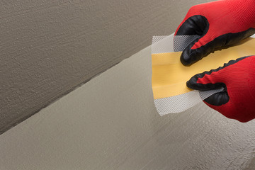 The worker shows how elastic and strong the waterproof tape is, sealing tape