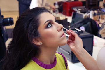 make-up artist makes a professional make-up model with blue eyes and dark hair