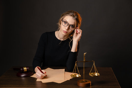 Pretty young woman in a glasses and in a black dress sitting and wrighting importaint document, notary woman ratify notary documents
