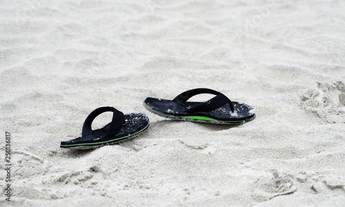 5a59a42a24c8 Flip-flops discarded on a sandy beach.