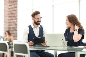 two employees discussing new ideas while sitting at the Desk