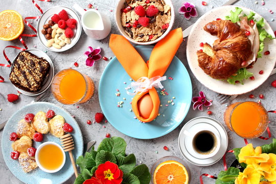 Breakfast food table. Festive brunch set, meal variety with pancakes, croissants, juice, fresh berries, granola and fresh fruits. Easter breakfast. Top view with copy space.
