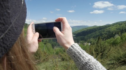 A woman is taking pictures against the background of big mountains and the green mountain river. on the phone. selfie or self-portrait on a smartphone. Enjoys adventure and travel concept