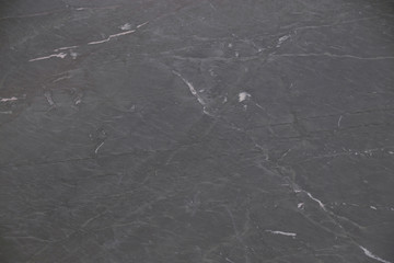 Closeup black soapstone stone with natural pattern texture background.