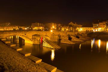 Night winter oldest stone bridge in central Europe above River Otava, Pisek, Czech Republic