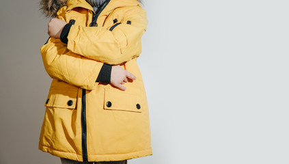 Front view of Child dressed in a yellow winter jacket with fur on the hood. The concept of dressing the child on winter days, the upcoming frosts. Children's fashion concept, clothes stores. Wall mural