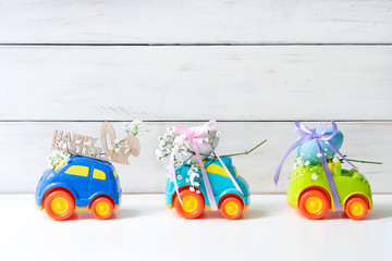 """Two Easter cars with an egg and a car with the inscription """"Happy Easter"""" on a white background, the concept of the approaching Easter"""