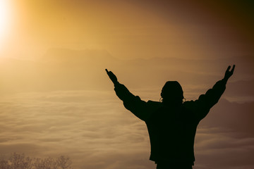 Man praying at sunset mountains raised hands Travel Lifestyle spiritual relaxation emotional concept, Freedom and travel adventure.