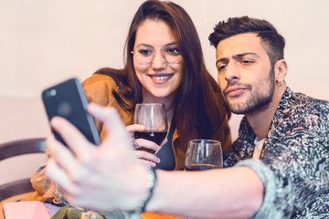 Young couple taking selfie sitting on a restaurant table while drinking a glass of wine. Couple lifestyle concept.