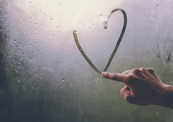 A man's hand is writing a heart-shaped glass window during a rain.