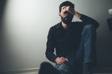 sad man sitting hand in face