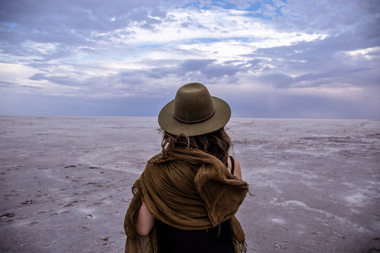 Kati Thanda Lake Eyre; woman in hat standing on salt lake looking out with clouds