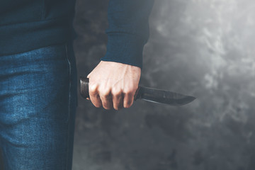 man hand knife on dark background