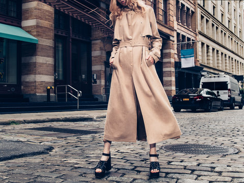 Fashionable woman wearing beige cotton long jacket and black high heels walking on city street of New York