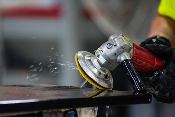 Worker polishing edge of granite stone countertop with grinder using water, close up