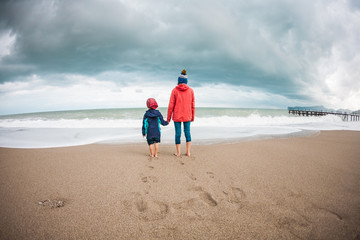 Barefoot boy with mother come into the sea.