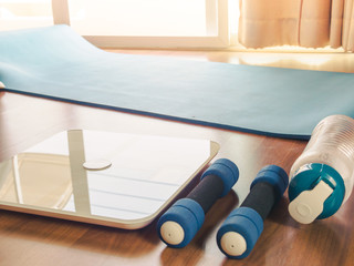 Fitness equipment and Weight loss concept form Weight Scale, dumbbells, mat yoga, handkerchief and drinking water, Flat lay on wooden floor of apartment for in home workout.