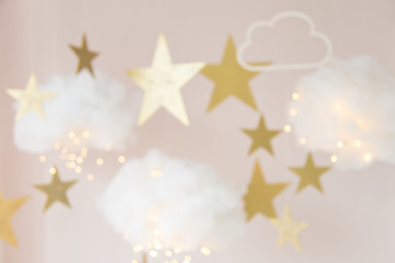 Blurred background. Christmas background. Christmas card. Clouds made of cotton with light, hanging by a thread. Star gold color. Cozy photo zone for a photo shoot. Children's room decoration.