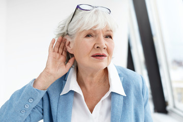 Come again please? Attractive mature woman wearing blue jacket and spectacles on her head eavesdropping. Stylish retired female in elegant clothes holding hand at her ear, suffering from hearing loss