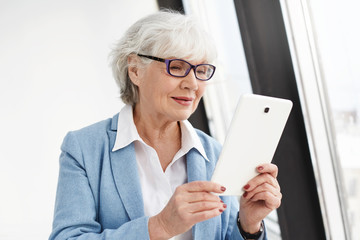 Staying connected. Modern smart elderly woman with gray hair posing isolated in glasses and formal clothes, reading electronic book or shopping online using digital tablet, having pleased happy look