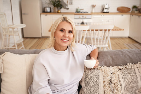 Portrait of attractive middle aged European female with blonde hair relaxing indoors with cup of coffee. Beautiful 45 year old woman sitting on couch in living room, enjoying tea, smiling at camera