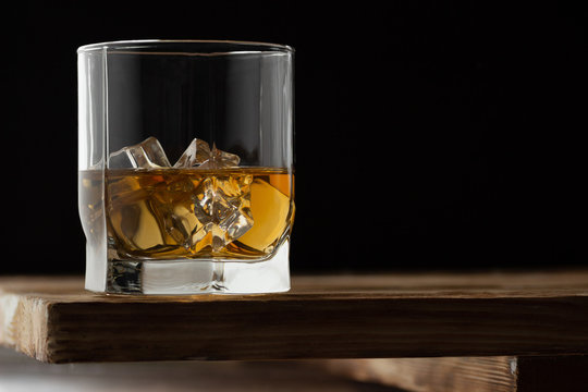 Glass of whiskey with ice cubes on a wooden table and dark background.