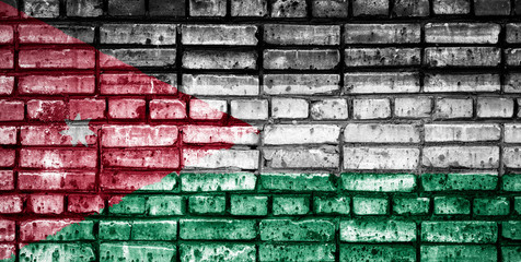 National flag of Jordan on a brick background. Concept image for Jordan: language , people and culture.