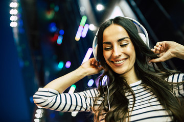 Close up portrait of attractive young happy woman in headphones with smart phone in hands outdoors