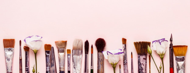 Art pink background. Row of different brushes and flowers. Banner format