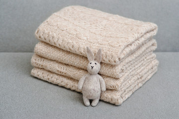 """Stack of knitted handmade plaids and wallow""""s hare"""
