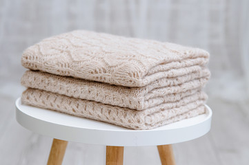 StA stack of knitted handmade plaids is lying on a tabouretack of knitted plaids made by hand